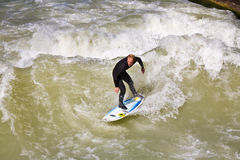 Surfer surfs at the Isar in huge Stock Image