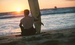 Surfer taking a break on the beach Stock Photo