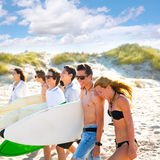 Surfer teen boys and girls group walking on beach. Sand royalty free stock photography