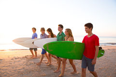 Surfer teen boys girls group walking on beach. At sunshine sunset Royalty Free Stock Photo