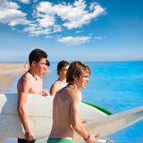Surfer teen boys talking on beach shore. Holding surfboards Stock Photo