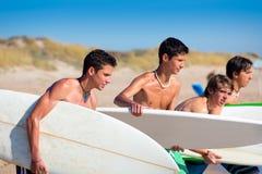 Surfer teen boys talking on beach shore. Holding surfboards Stock Photography