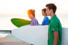 Surfer teen boys walking at beach shore. Surfer teen boys group walking at beach shore on sunshine or sunset Royalty Free Stock Photo