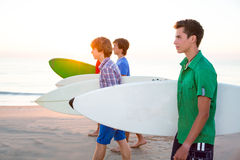 Surfer teen boys walking at beach shore. Surfer teen boys group walking at beach shore on sunshine or sunset Stock Photos