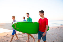 Surfer teen boys walking at beach shore. Surfer teen boys group walking at beach shore on sunshine or sunset Royalty Free Stock Photography