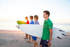 Surfer teenager boys walking at beach shore Stock Photos