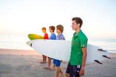 Surfer teenager boys walking at beach shore. Surfer teenager boys group walking at beach shore on sunshine or sunset Stock Photos