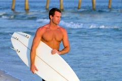 Surfer-tragendes Surfbrett Lizenzfreies Stockfoto