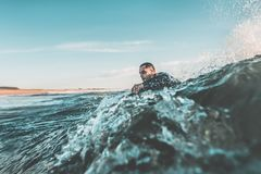 Surfer trying to catch a wave. Young man with the water up to the neck trying to catch a wave with his bodyboard among the rough waters of the sea. Extreme water Stock Photo