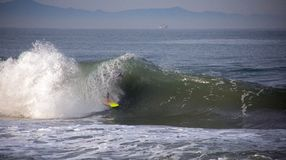 Surfer tubed in wave at sandbar where the Santa Clara River empties into the Pacific Ocean in Ventura California USA. Surfer tubed in wave at sandbar where the royalty free stock images