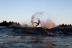 Surfer Turn Fins Free on Sunset. A surfer performs an aerial manoeuvre during sunset in front of a beach lined with pine trees. The orange glow of the sunset is Stock Photography