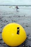 Surfer und irische Windsurfenvereinigungsgelbboje Stockfotos