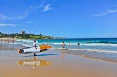 Surfer und Schwimmer bei Coogee setzen an einem sonnigen Tag auf den Strand Lizenzfreie Stockfotos