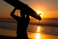 Surfer und Vorstand in der Abendsonne Lizenzfreies Stockfoto