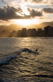 Surfer under Sunset. Solitary surfer riding a wave in Ipanema Beach under the glow of the sunset. Rio de Janeiro, Brazil Royalty Free Stock Photos