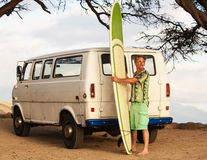 Surfer with Van and Surfboard. Grinning male surfer with surfboard and van on beach Royalty Free Stock Photos