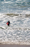 Surfer wading into sea with surfboard Stock Images