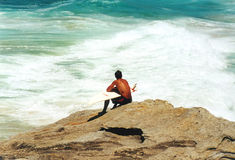 Surfer Waiting. On a rock Royalty Free Stock Images
