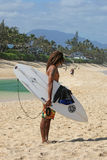 Surfer waiting on beach. For good waves on North Shore of Oahu, Hawaii, holding surfboard Royalty Free Stock Photography