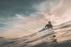 Surfer waiting for a big wave at sunset. Young man waits in the sea, near the coast, on his surfboard, a big wave at sunset. Extreme water sports and outdoor Royalty Free Stock Photography