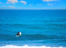 Surfer waiting for the wave. Under a huge cloud Royalty Free Stock Images