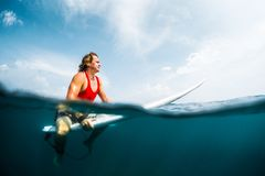 Young surfer waits wave in the ocean. Surfer waits wave in an ocean, split shot with underwater view Royalty Free Stock Images
