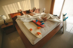 Surfer wakes up. With his boards in bed Stock Image