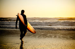Surfer walking. On the beach with the waves at sunset in Portugal royalty free stock image
