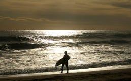 Surfer walking  along the beach Royalty Free Stock Photo