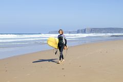 Surfer walking along the beach Royalty Free Stock Photo