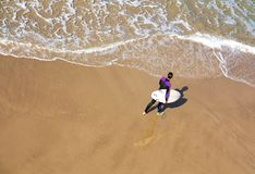 Surfer walking along the sea was shot from top stock photography