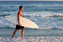 Surfer Walking Beach. Surfer carrying his surfboard walks along the beach Stock Photography