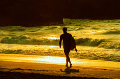 Surfer walking on the beach. In the evening light, cross processed effect Royalty Free Stock Image