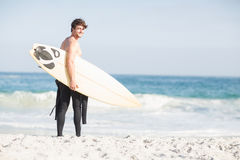Surfer walking on the beach with a surfboard Stock Photos