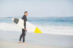 Surfer walking on the beach with a surfboard. Surfer with a surfboard walking on the beach on a sunny day Royalty Free Stock Photos