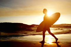 Surfer walking on beach with surfboard during sunset. Portrait of a surfer walking on beach with surfboard during sunset Stock Image