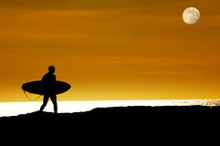 Surfer walking on cliffs to last ride Stock Photography