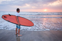 Surfer walking on coast in Bali Stock Photos