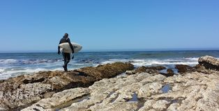 Surfer walking off the rocks into the ocean. In Southern California stock photography