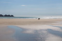 Surfer walking over wide sandy summer beach with sea and rocky c Stock Images