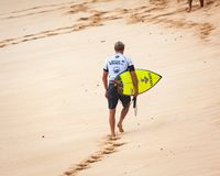Surfer Walking on Sunset Beach Hawaii. SUNSET BEACH, HAWAII, USA - DECEMBER 2: Competitive surfer walking on beach at the 2017 Vans World Cup of Surfing Stock Photo