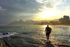 Surfer walking at sunset. Over the rocks in Arpoador beach at Ipanema in Rio de Janeiro Royalty Free Stock Photos
