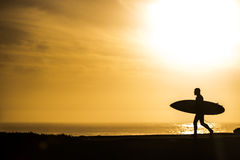 Surfer walking in the sunset in Santa Cruz, California. EUA Stock Photos