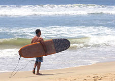 Surfer walking with surfboard stock photography