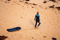 A Surfer Walking Towards Bass Straight. A surfer walks on the sand towards Bass Straight at Logan`s Beach on The Great Ocean Road Australia stock photo