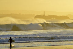 Surfer walking towards the sea at sunrise in Santander Royalty Free Stock Photos
