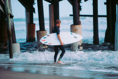 Surfer walking under pier Stock Images