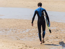 Surfer walking into the warter on the sun at the beach.  Stock Image