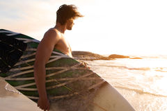 Surfer walking by water looking at waves Stock Photo