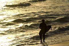 Surfer walking on the water. At tropical sunset Royalty Free Stock Photos